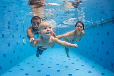 Happy full family - mother father baby son learn to swim dive underwater with fun in pool to keep fit. Healthy lifestyle active parent people water sport activity swimming lesson. Focus on child